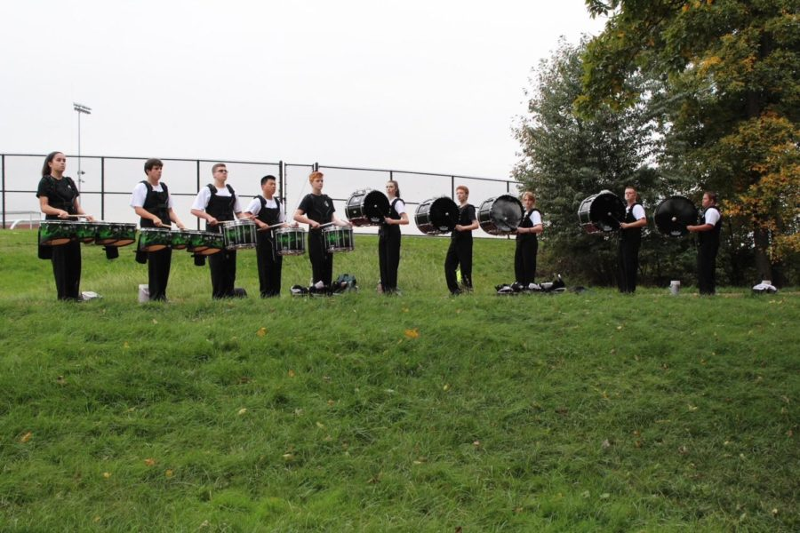 The drumline warms up in their designated area.
