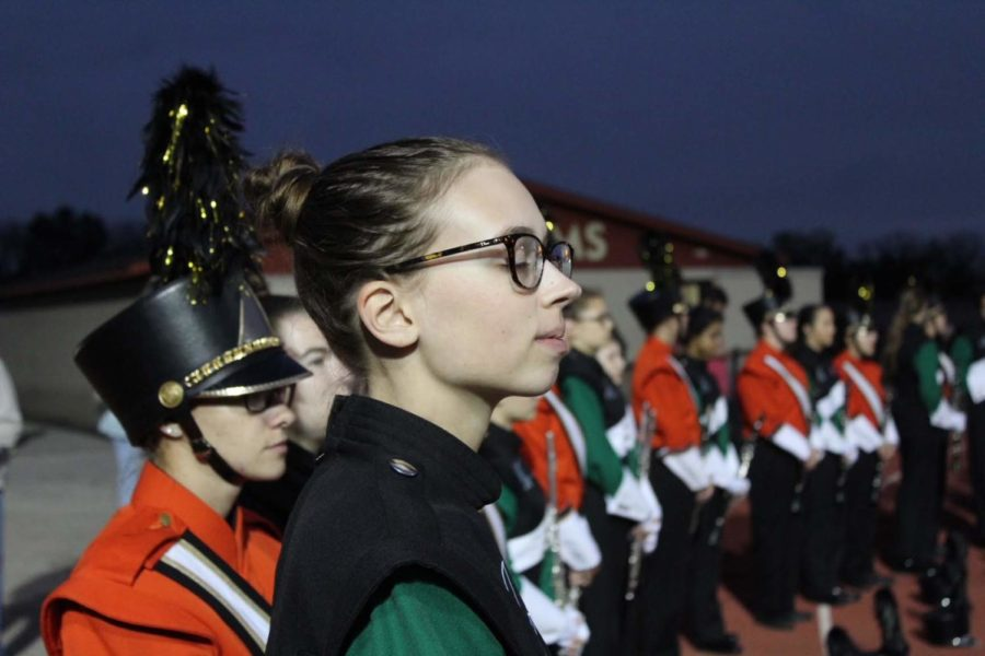 Piccolo player Cecilia Weaver takes a moment to take in the sounds of a Friday night football game.