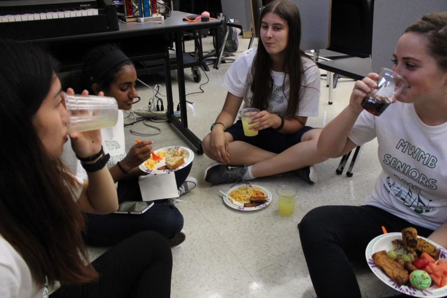 (from left) Amy Ouyang, Alexis Gordon, Rebekah Varghese and Samantha Haas eat the Friday food prepared by the band parents.