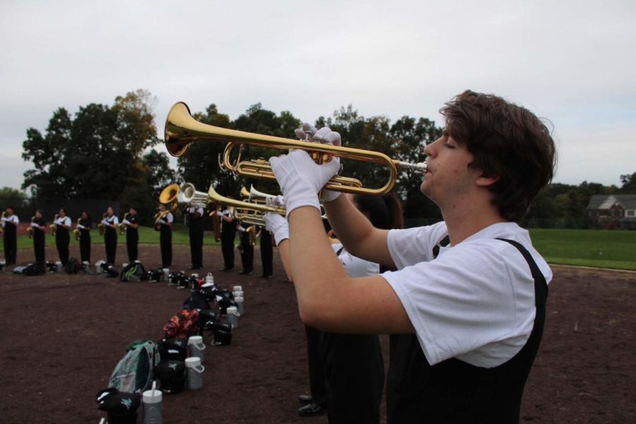Trumpet player Rocco Cavallo warms up by blowing counted air through his instrument.