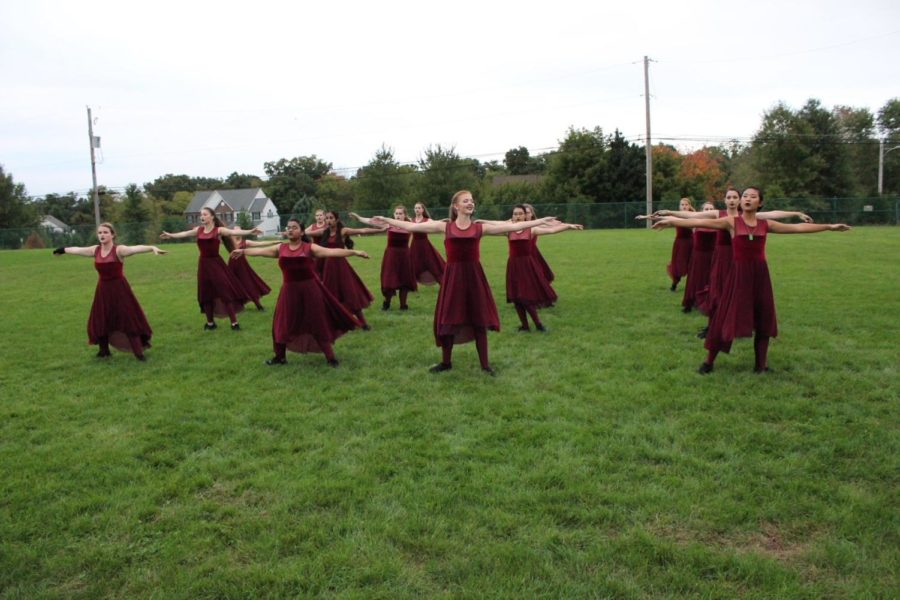 The color guard warms up with their across-the-field body exercise.