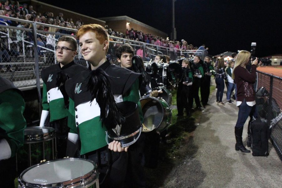 The band walks to the bleachers after playing the National Anthem.