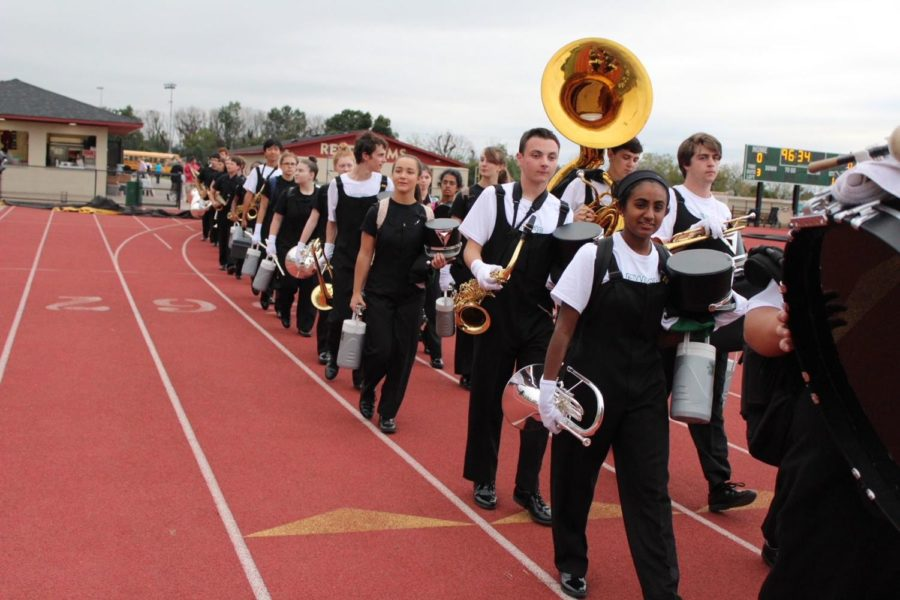 The marching band walks in twos on their way to pre-game practice.