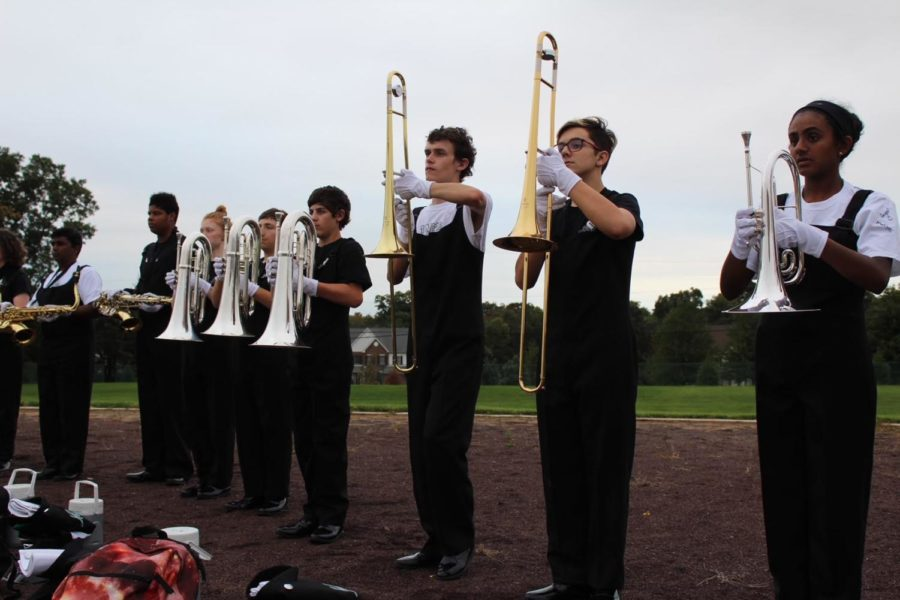 The mellophones, trombones, baritones and tenor saxophones stand at set waiting for the drum major to begin conducting.