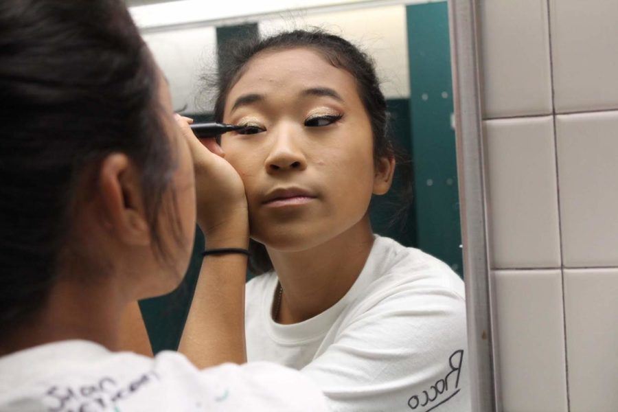 Color guard captain, Jen Chang, prepares for the night by putting on her show makeup.