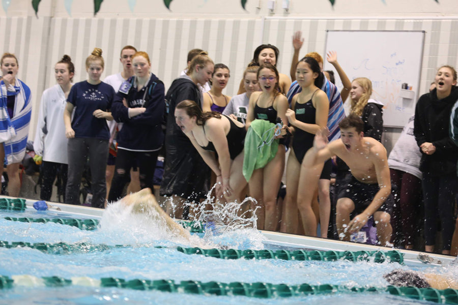 Girls from the team cheer on their teammates during the 400 free relay.
