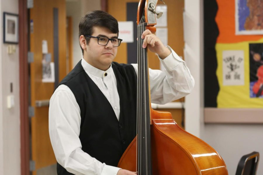 Max Kozol plucks his bass while waiting for the rest of the students to tune their instruments.