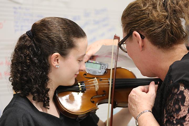 Ms. Magann, orchestra director, helps freshman Abigail Thornton tune her violin.