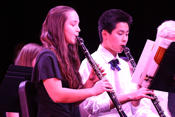 Clarinet players focus on their sheet music during The Promise of Living from The Tenderland Suite.