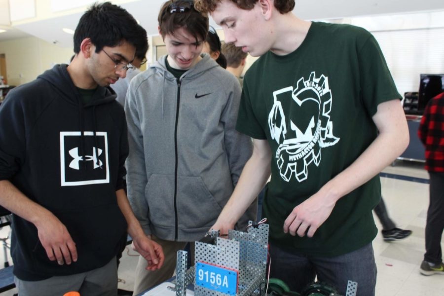 (from left) Senior Anurag Rao, Junior PJ Rossetti, and Senior Eli Smith discuss strategy and examine robot 9156A prior to the VEX competition on Feb. .