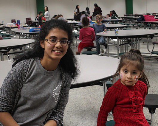 Varsha Bhat, freshman, sits with one of the children who opted to get her face painted.