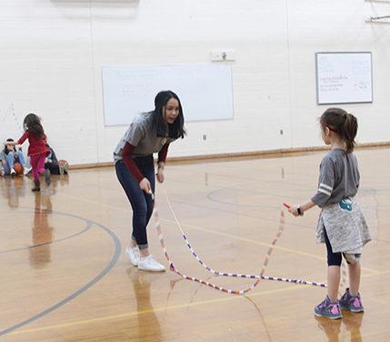 Caitlin Alano teaches a little girl how to double dutch.