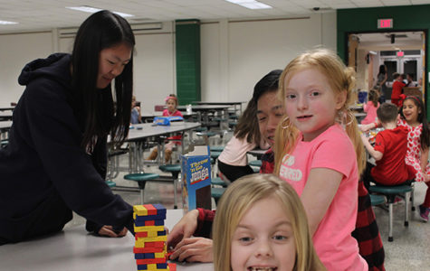 Club members and kids prepared to play Jenga in the cafeteria.
