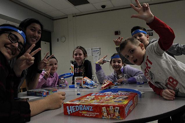 (from left) Hira Khattak and Amy Ouyang, high school seniors, helped the kids play Headbanz.