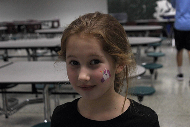 A child participating in the event displays her unicorn face paint.