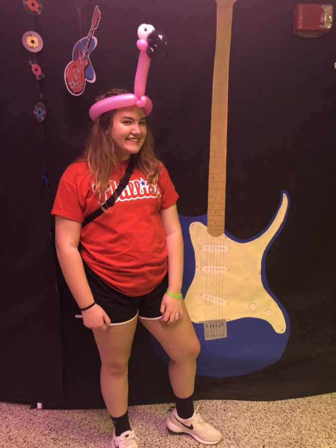 Camille Conard, a junior, poses with her flamingo hat made by the balloon artist.