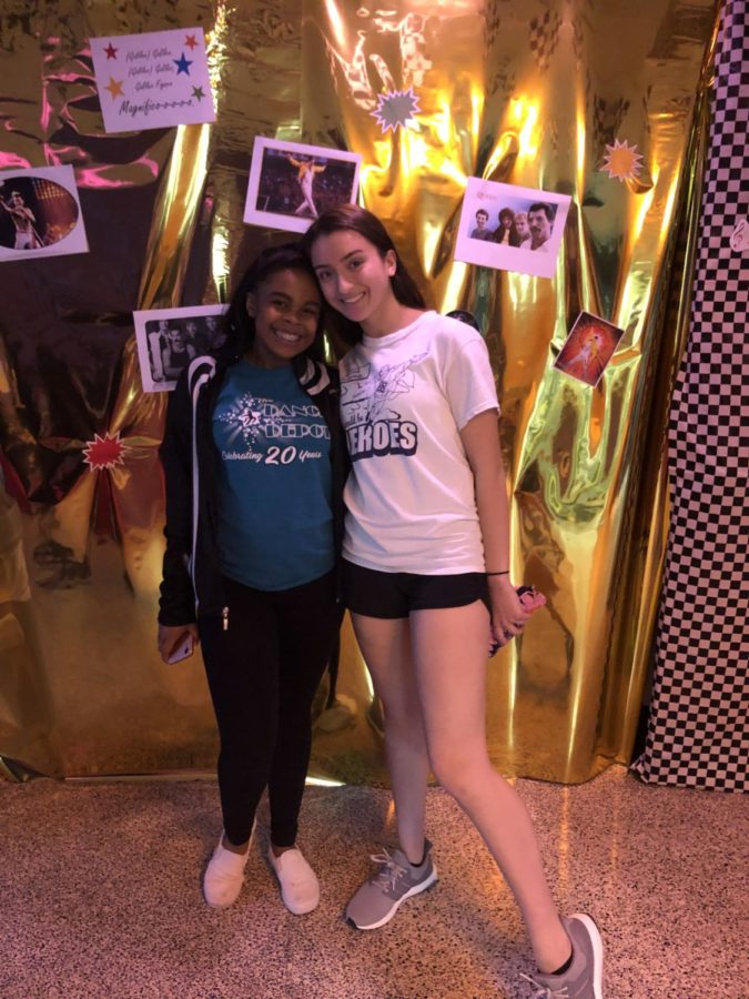 Sarah Hunsicker and Siani Ford-Barkley stand together in front of a wall dedicated to Queen.