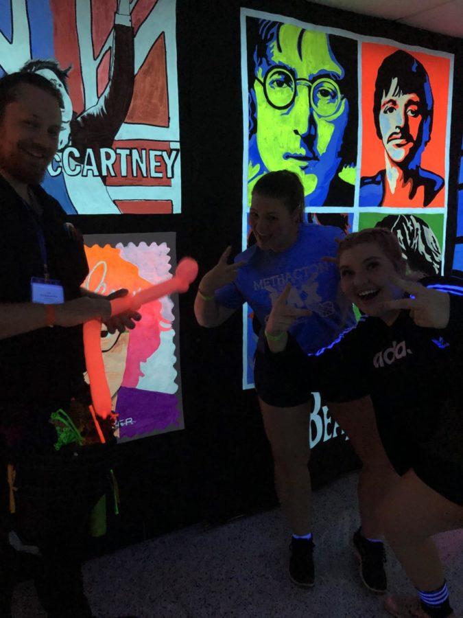 "Lauren McDonald and Katherine Mcgrath pose with the balloon artist in the ""blacklight hallway""."