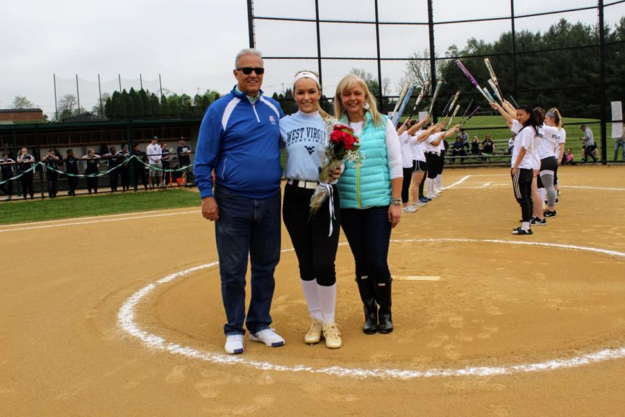 Taylor Angelillis stands with her parents after walking through the traditional bat passage.