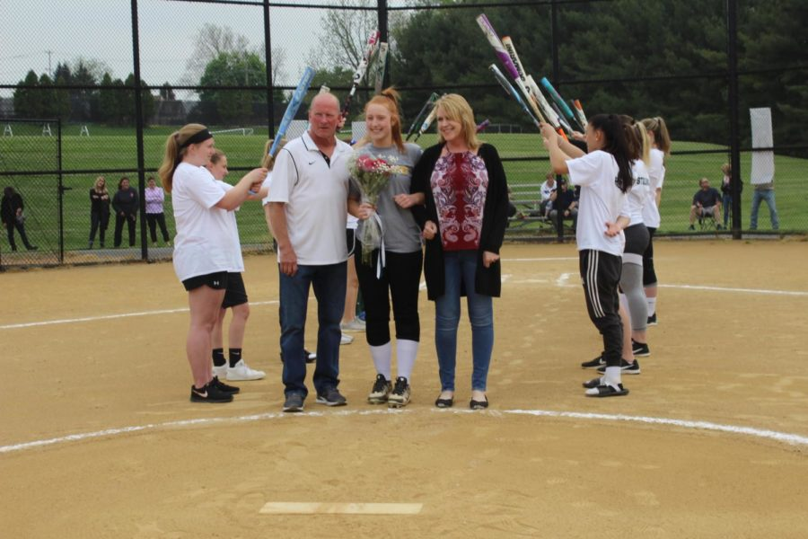 Sara Markley walks with her parents past the pitcher's mound.