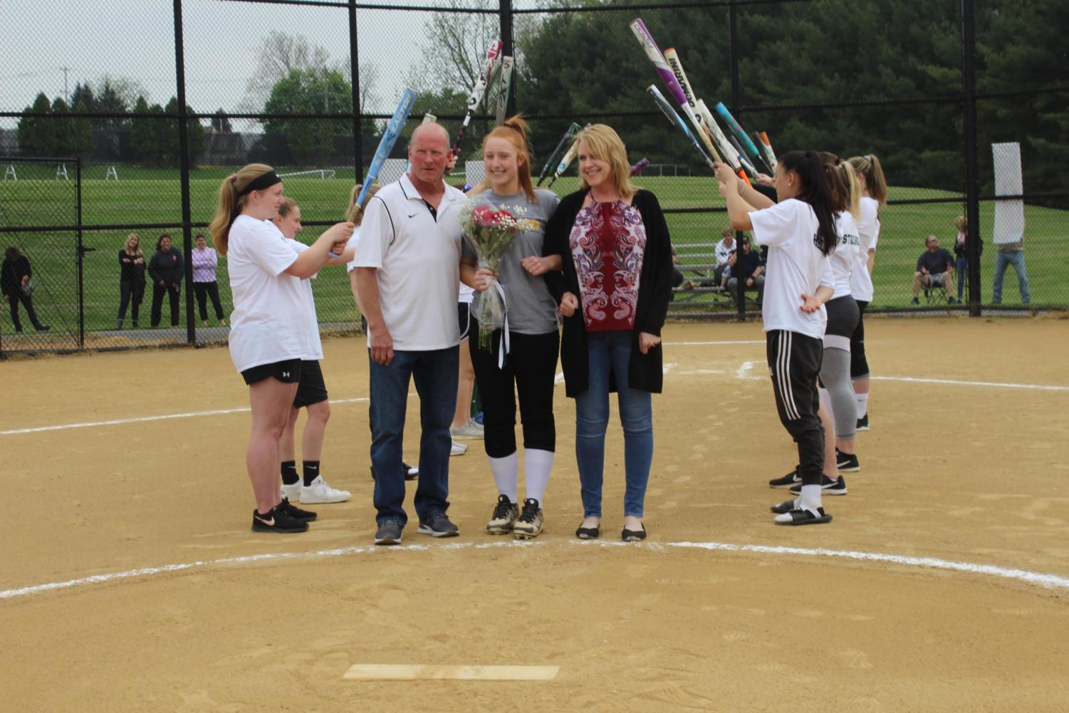 Sara+Markley+walks+with+her+parents+past+the+pitcher%27s+mound.%0A