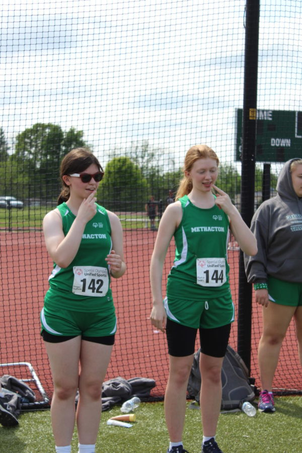 Freshmen Regan and Madelyn practiced their national anthem sign language prior to the meet.