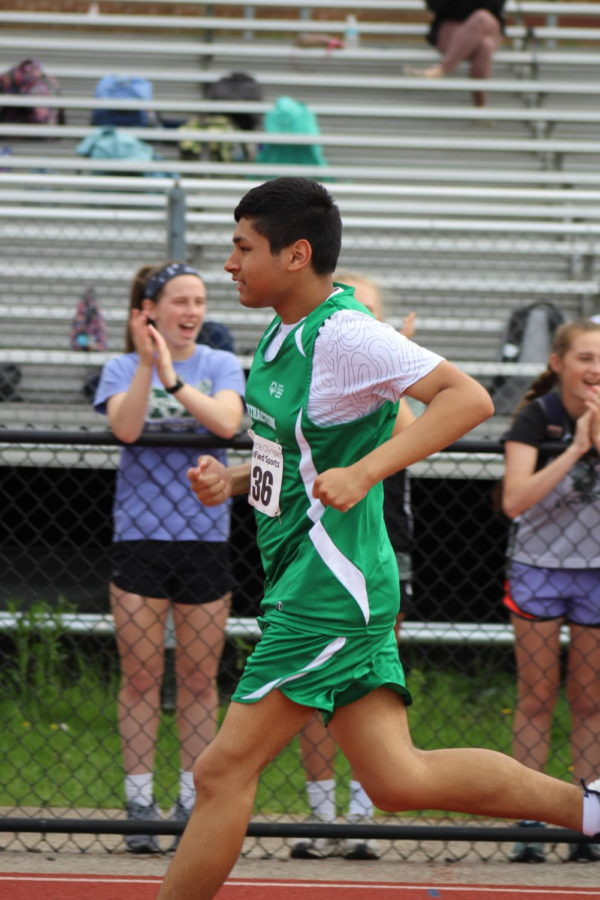 Sophomore Javier Altimirano ran while the girls lacrosse team cheered him on.