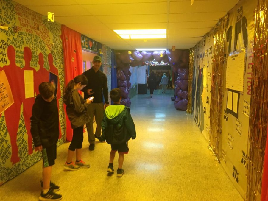 Adults and children walk through the halls of Methacton Post Prom and take pictures.