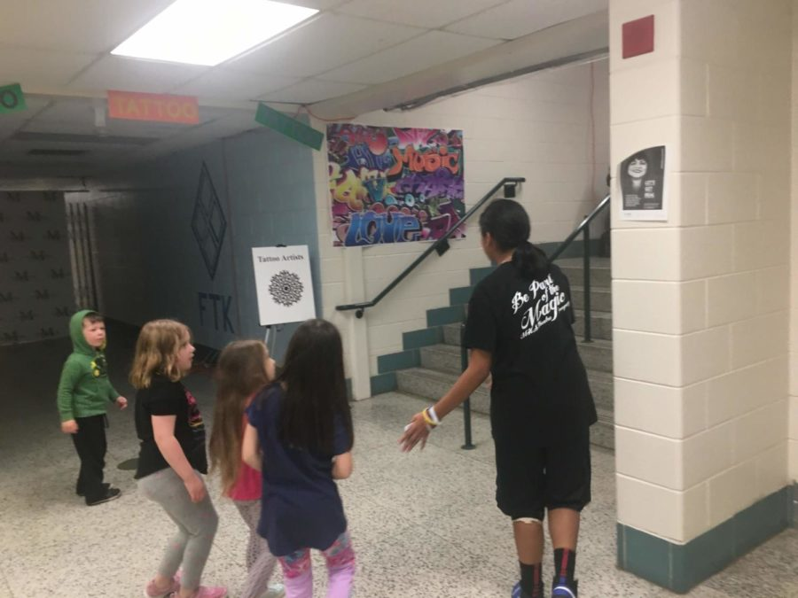 Sophomore Julianna Dolin gives elementary school kids a tour of post prom .