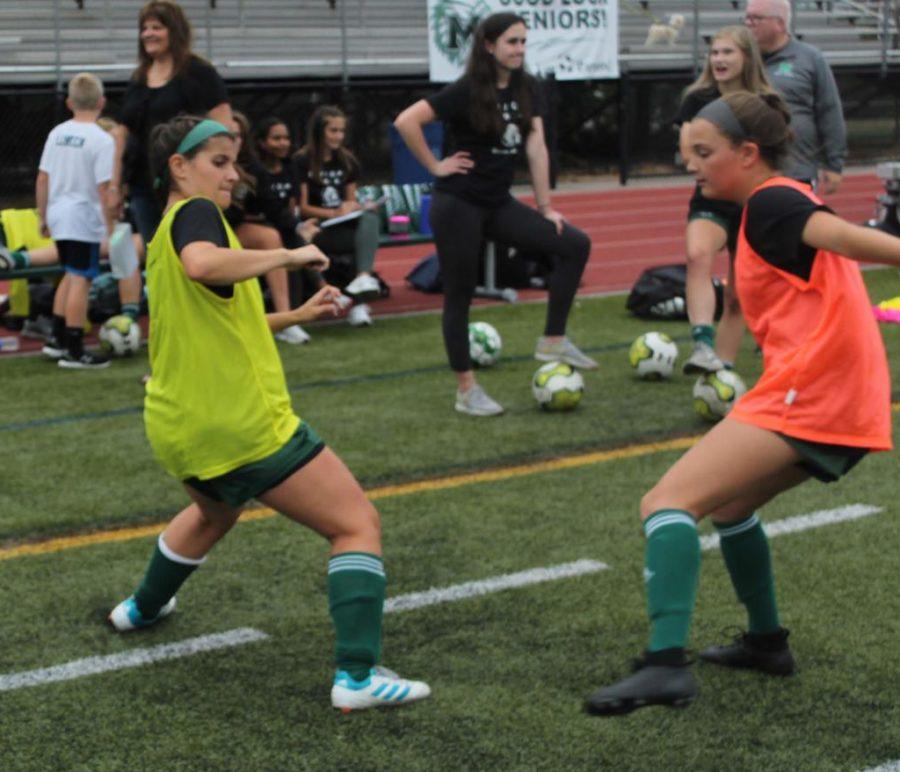(Right) Freshman Mackenzie Coupe defends senior Rachel O'Toole during warmups.