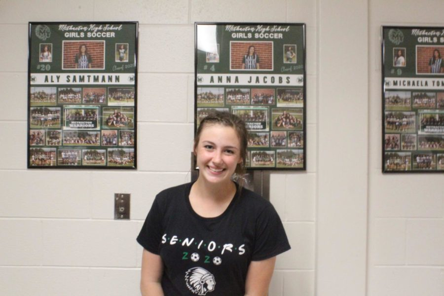 Senior Anna Jacobs poses with her collage.