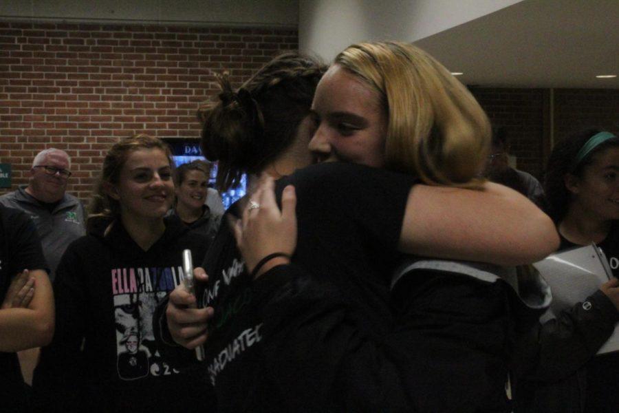 Junior Jessica Lineen and senior Anna Jacobs embrace after Lineen's speech.
