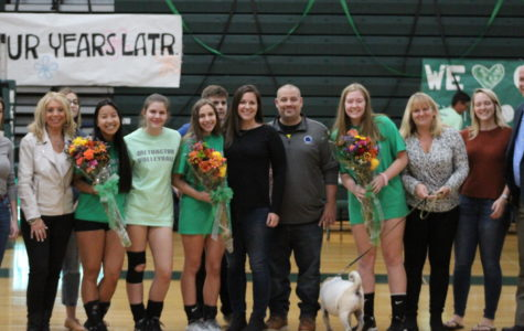 All three seniors pose on the volleyball court for a photo with their friends and family.