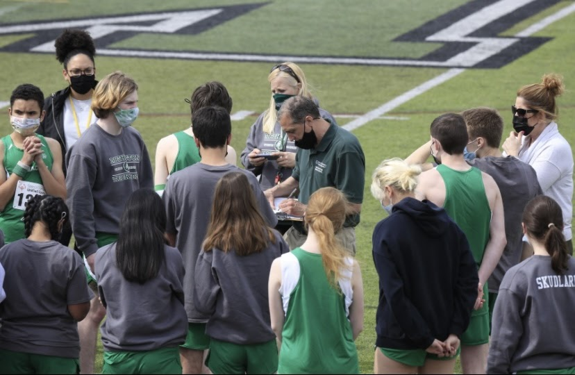 (center) Mr. Alzamora and Ms. Quintois, Unified Track and Field sponsors, go over the order of events list with athletes minutes before the Warriors faced off against Perkiomen Valley and Lower Moreland on April 20.