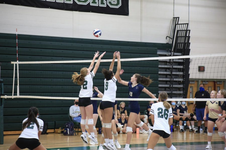 Outside hitter, Mandy Baldwin (12), and the middle, Bianca Robinson (9), attempt a block during a Spring-Ford attack.