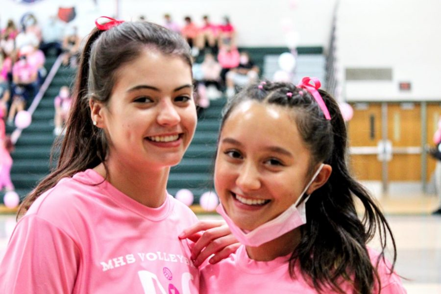 Varsity team captains Mel Eglinton and Meg Haftl support the junior varsity squad and spread awareness for breast cancer by cheering in pink.